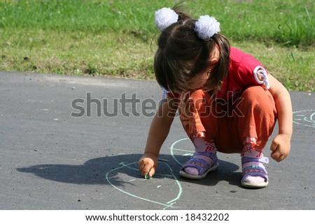 little girl is drawing on asphalt