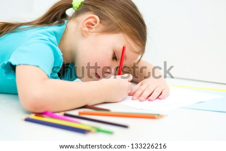 Little girl is drawing using color pencils while laying on floor - stock photo