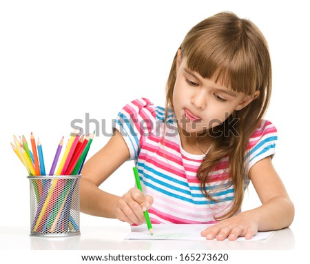 Little girl is drawing using color pencils while sitting at table and sticking her tongue out, isolated over white