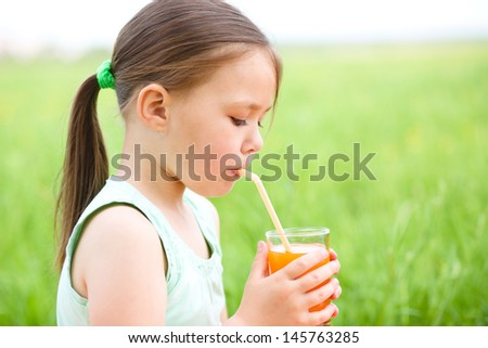 Little girl is drinking orange juice using straw while sitting on green grass