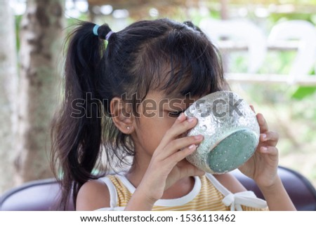 Little girl is drinking water from a water dipper to quench thirst and refresh the body. #1536113462