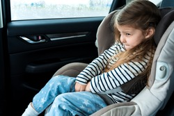 Little girl is driving in car. Kid child wants to go to toilet, pee and endures. Traveling, riding on road in safe baby seats with child belts. Fun family trip, activity with parents.