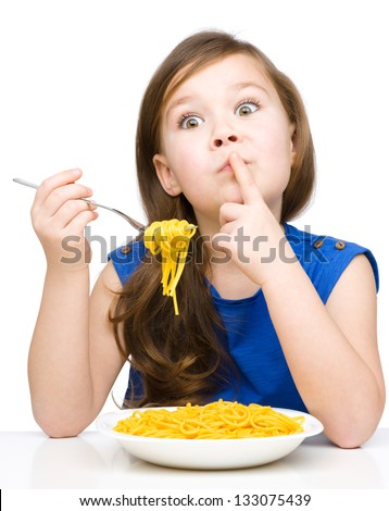 Little girl is eating spaghetti while showing hush gesture, isolated over white
