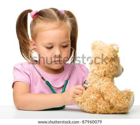 Little girl is examining her teddy bear using stethoscope, isolated over white - stock photo