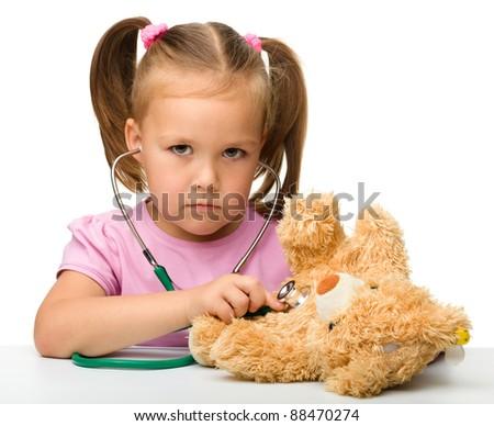 Little girl is examining her teddy bear using stethoscope, isolated over white
