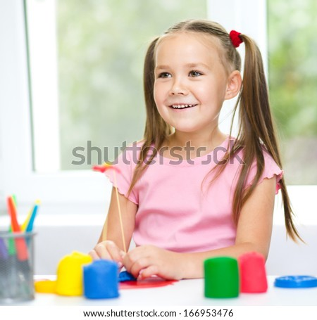 Little girl is having fun while playing with plasticine