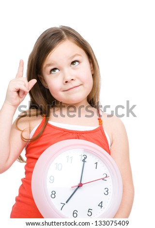 Little girl is holding big clock and pointing up, isolated over white