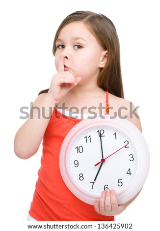 Little girl is holding big clock and showing hush gesture, isolated over white
