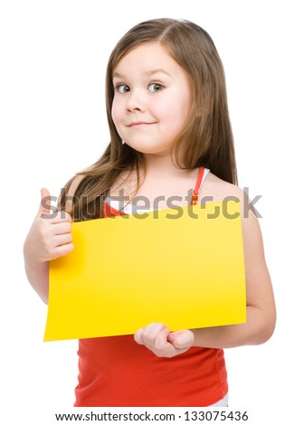Little girl is holding blank yellow banner and showing thumb up gesture, isolated over white