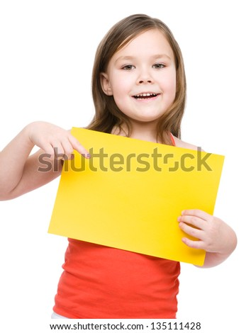 Little girl is holding blank yellow banner, isolated over white