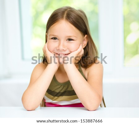 Little girl is holding her face while listening to somebody, isolated over white