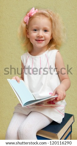Little girl is looking through the book