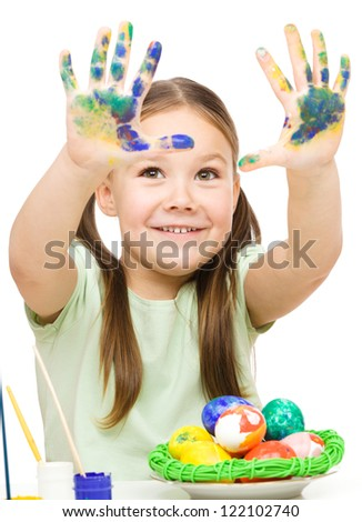 Little girl is painting eggs preparing for Easter showing her hands, isolated over white