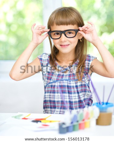 Little girl is painting with gouache while sitting at table and wearing glasses