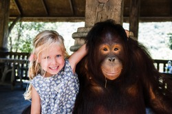 little girl is photographed with a big monkey