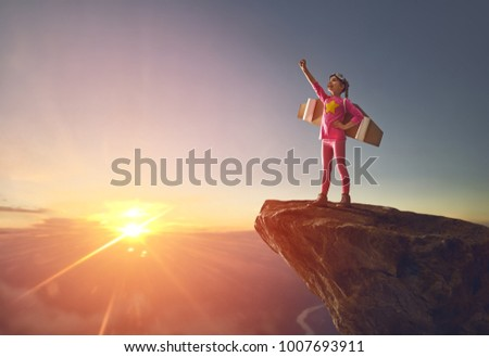 Little girl is playing astronaut. Child on the background of sunset sky. Kid in costume is dreaming of becoming a spaceman. #1007693911