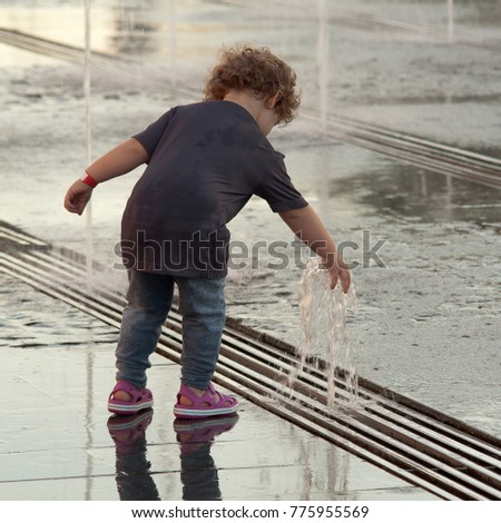 little girl is playing by the fountain in the summer city #775955569