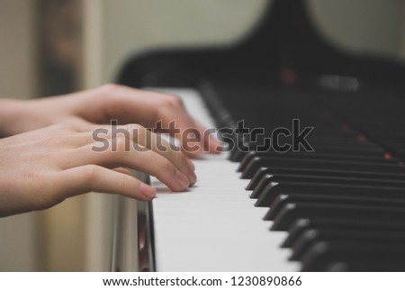 Little girl is playing the grand piano. #1230890866