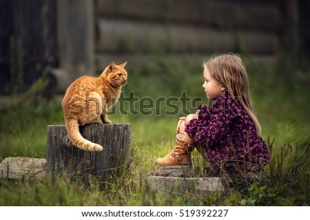 Little girl is playing with a big red cat  in the country in Russia. Image with selective focus and toning