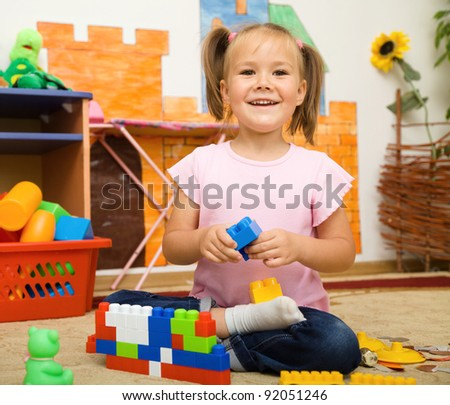 Little girl is playing with building bricks in preschool while laying on floor