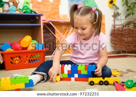 Little girl is playing with building bricks in preschool while sitting on floor - stock photo