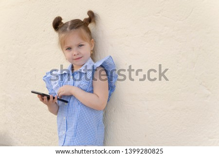 Little girl is playing with smartphone. ?hild touches the touch screen. Copy space #1399280825