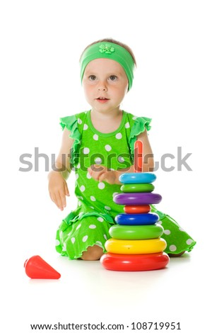 Little girl is playing with toy pyramid on a white background