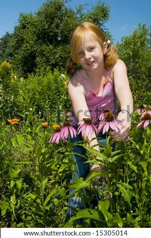 Little girl is plucking flowers in the garden