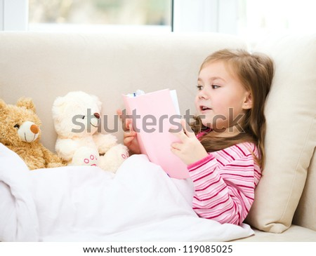 Little girl is reading a book for her teddy bears while laying on white couch