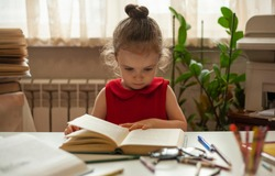 Little girl is reading a book with interest. Preschool education. Education and science. International Literacy Day.