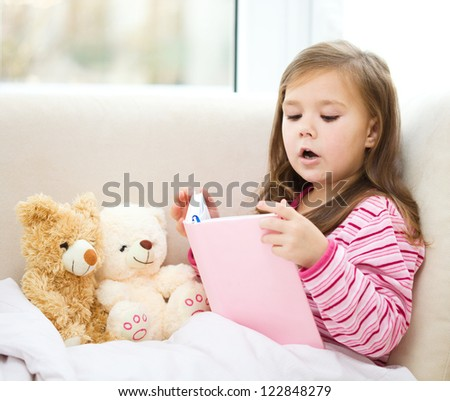 Little girl is reading a story for her teddy bears while laying in bed and wearing pajama, indoor shoot - stock photo