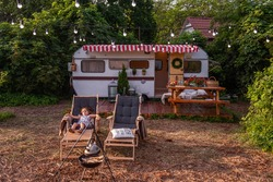 Little girl is resting on wooden deck chair near the trailer track. Rest of the whole family outside the city, fun outdoor travel. Picnic camping vacation with children. Kettle boiling over the fire