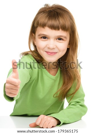 Little girl is showing thumb up sign, isolated over white