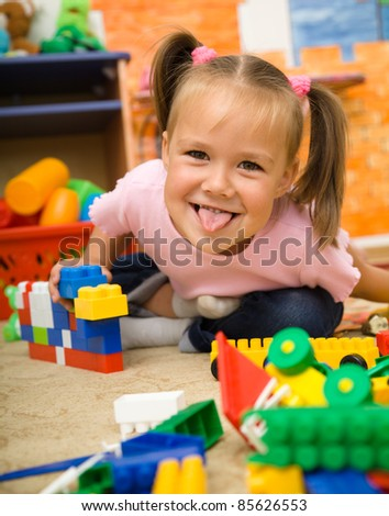 Little girl is showing tongue while playing with building bricks in preschool