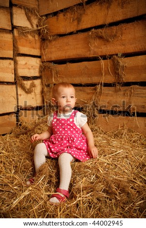 Little girl is sitting on pile of straw in hayloft against the wall of boards. Vertical format.