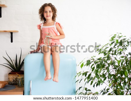 Little girl is sitting on the fridge. Sits on a beautiful retro refrigerator of blue color, stylish interior. #1477951400