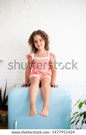Little girl is sitting on the fridge. Sits on a beautiful retro refrigerator of blue color, stylish interior.