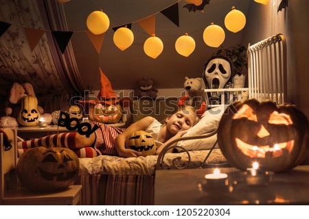 Little girl is sleeping in a children's bedroom decorated for Halloween