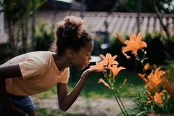 Little girl is smelling flowers