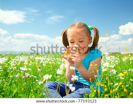 Little girl is smelling flowers while sitting on green meadow - stock photo
