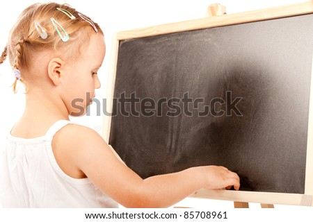 little girl is standing at the blackboard in studio