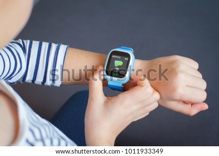 Little girl is using smartwatch phone.