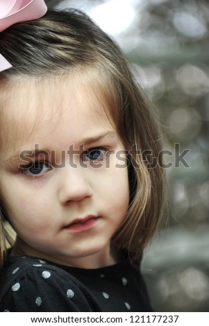 Little girl  is very solemn as she looks into the camera.  She has on a pink bow and black polka dotted shirt.