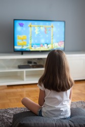 little girl is watching cartoons and playing video games on TV at home. Selective focus.