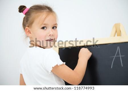 Little girl is writing letters on a blackboard