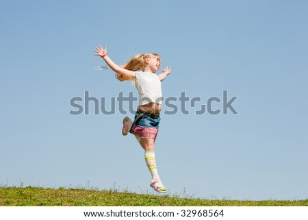 Little girl jumping against beautiful sky - stock photo