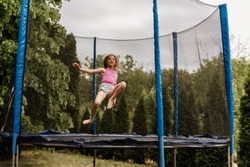 Little girl jumping in trampoline outdoors on an overcast day.