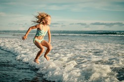 little girl jumping on the beach in the day time