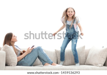 little girl jumping on the couch on the couch in the living room #1459536293