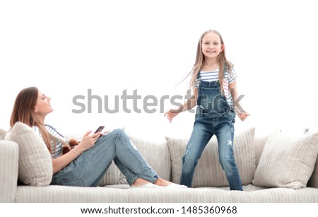 little girl jumping on the couch on the couch in the living room #1485360968